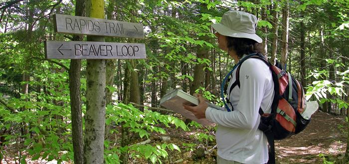 Researcher takes notes along hiking trail.